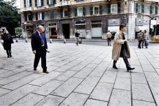 Genova, 30/03/2012 - Passanti davanti al palazzo della prefettura di Genova.